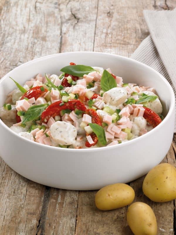 Aardappelsalade met kippenwit, geconfijte tomaat, komkommer, basilicum en pestodressing