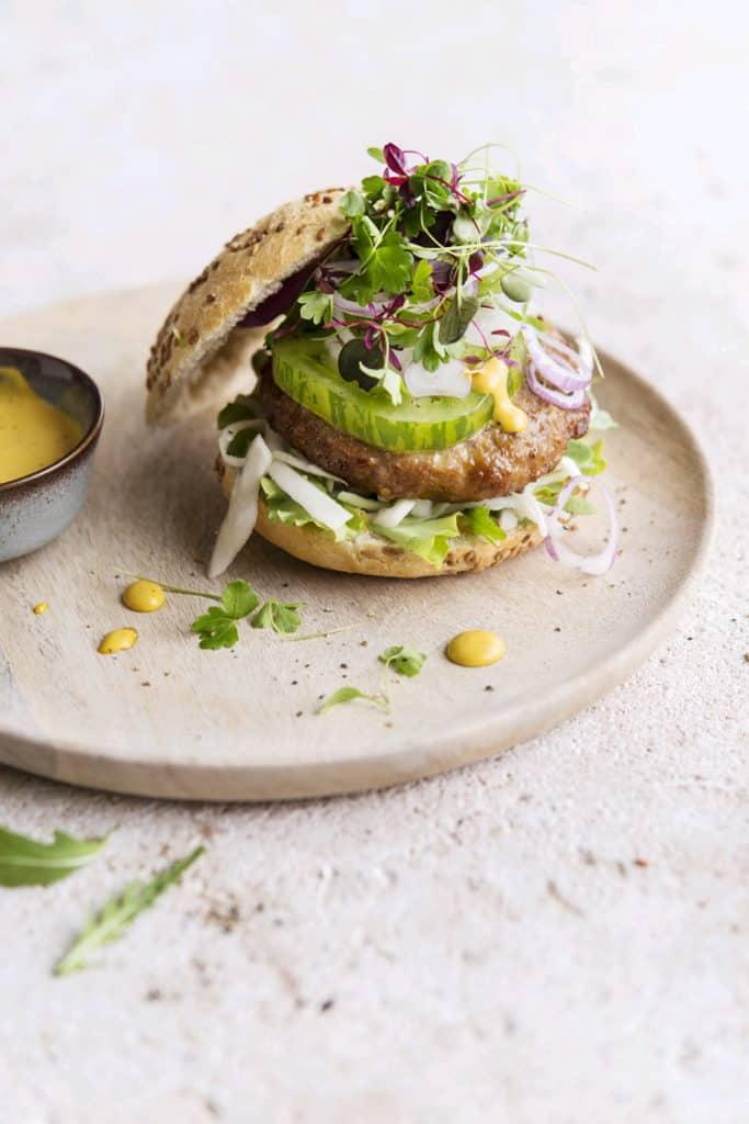 Broodje met een Premium kalkoenburger, frisse groentjes en mosterdsaus